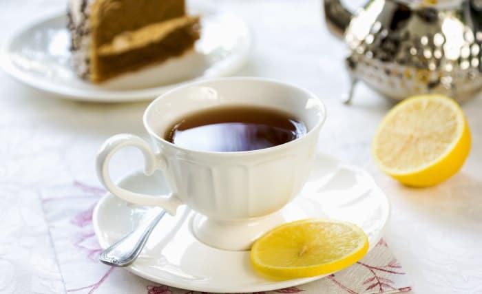 kop te på bord med kage i baggrunden
