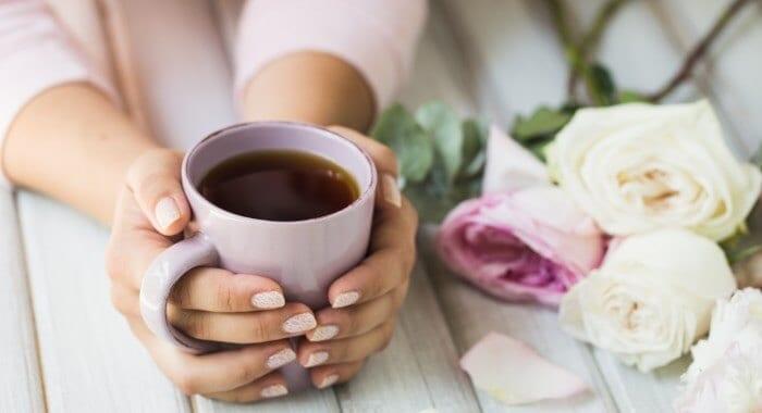 Kvinde holder en kop te på et bord med blomster